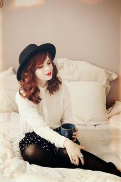 white blouse. black and white polka dot skirt. black hat.