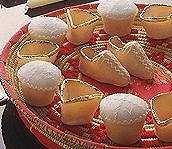 CANDELAUS Delicatissimi e gustosi, dono prezioso dell'arte pasticciera femminile del Campidano, sono piccoli dolci canditi che assumono le più svariate forme: tronco-conica, a scarpetta, di animali. Is Candelaus, sono costituiti da sottilissime sfoglie di pasta che avvolgono un composto di finissime scaglie di mandorle, lavorate attentamente con lo zucchero e l'acqua di fior d'aranci. A cottura avvenuta, il dolce viene ricoperto di glassa e decorato con abilità artigianale dalle donne che con fogli dorati creano disegni caratteristici, spesso decorati con palline argentate.