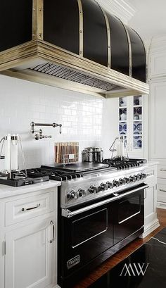 Gourmet kitchen features a black barrel hood with stainless steel straps which stands over a swing-arm pot filler and a black Viking Range. Kitchen Hoods, New Kitchen, Kitchen Dining, Kitchen Decor, Kitchen Cabinets, Kitchen Appliances, Kitchen White, Kitchen Ideas, White Cabinets
