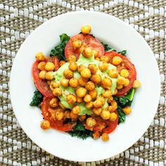 Pan-fried tomatoes with roasted chickpeas, kale, and lemon avocado cream.