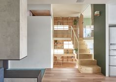 Taiwan apartment renovation by Hao Design includes a new floor with a wooden bridge-like corridor that connects a master bedroom to a walk-in wardrobe on the mezzanine level.