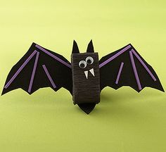 Add crafts-foam wings to a box of candy wrapped in crepe paper for a bat that's simple enough for the kids to make. Cover the sides of a mini box of candy with black crepe paper, taping the pieces in place. Cut out black wings from crafts foam (for young kids, trace the shape onto foam beforehand) and glue on purple foam details. Use our download as a template for the bat wings.