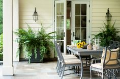 The covered porch, with both dining and living spaces, overlooks a pristine setting cultivated by Alec Michaelides.