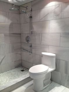 Use large format tiles through out your entire bathroom and add some mosaics on the shower floor!