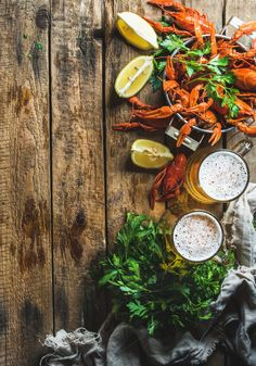 #Wheat beer and boiled crayfish Two pints of wheat beer and boiled crayfish with lemon and parsley over old wooden rustic background top view copy space