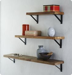 i like these brackets. i think dark wood with black brackets above the couch, as long as the brackets are thin.