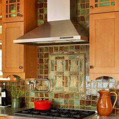 Inspired by Nature - Handmade, embossed tiles on this backsplash reflect the detailed craftsmanship evident throughout the entire kitchen. In shades of brown and green, the tiles bring a hint of nature into the cooking zone and suit the kitchen's Arts and Crafts design. A mix of rectangular and square shapes emphasizes the kitchen's simple lines and forms a unique design over the range.