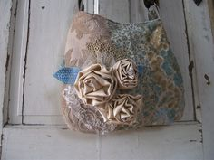 One of a kind shabby handbag. Luxurious vintage fabric makes this bag a show stopper. Stunning blues, browns, and neutral tones makes this a go-with-every-outfit bag. The front has 3 different textured fabrics and 3 silk rosettes with some glitzy jewels. Also has a piece of vintage wedding dress lace to adorn the front. Two pockets inside with a zipper compartment.  Magnetic snap closure and a bigger pocket on the outside will make this your favorite handbag.