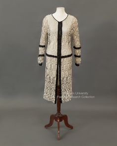 Dress-coat with long sleeves, cream cord embroidery on black net with black silk ribbon decorative insets, extended back panel, c.1920s. No label. FRC1981.07.001