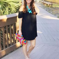 Cute black off the shoulder dress that is perfect for Spring and summer. Paired with a turquoise necklace and pom pom clutch for a great casual outfit.