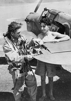 The Drive for Messina 10 July - 17 August 1943: Flying Officer Colin Edmends from Australia and his fitter, D McMinnemy, inspect the tail of his Curtiss Kittyhawk after it was damaged during a sortie over Catania.  f