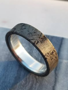 This is the premier ring of our Fiery Descent Collection at Ferro Lithic Design. We build the ring from a piece of the Muonionalusta meteorite that fell in Scandinavia approximately one million years ago. The band then receives a .925 sterling silver liner to provide style, comfort