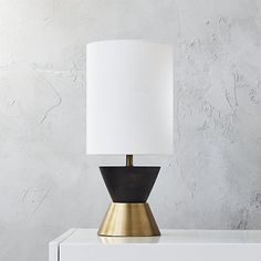 Shop mister table lamp.   Metallic and black edge masculine in this sculptural table lamp.  Linen shade adds texture and filters light while the base reflects a warm gold glow.  Arrives ready to go with CFL bulb included (13W).