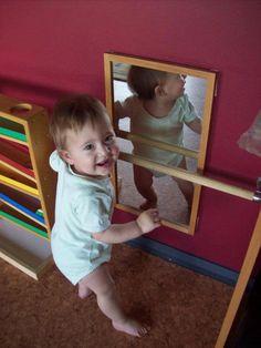 Barra fixada para estimular o bebê e espelho no quarto