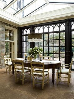 This dining room is the epitome of elegance with simple furniture, white roses, and ornate French doors.