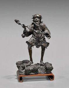 """(SOLD) Antique Japanese Bronze Okimono of an Immortal Sennin Figure (likely Gama Sennin) Standing on Rockery Base, right knee bent at a 90° angle; the left hand holds a Gourd from which rises a thin scaled Dragon, the two forming the Sennin's Magical 'Staff.' Highly skilled detail of sculpture & incised design offer a breathtaking simultaneity of realism and magical whimsy! Height 15"""" (38cm); Width 9.5"""" (24cm); Weight 15 lbs (6.5 kg). Circa Late Edo to Meiji Period (19th Century); Imperial…"""