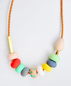 "Peach Polka Necklace    -  Clay, wood and brass on woven leather cord    -  31"" long    -  Lobster clasp clo"