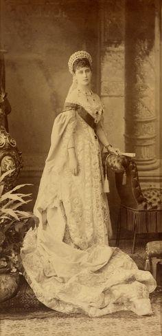 Grã-duquesa Elisabeth Feodorovna em 1885. Ela está em pé de frente para a câmera, segurando um leque em sua mão esquerda e apoiando-se na cadeira ao lado dela para a direita. Ela está usando um vestido da corte imperial, incluindo um longo comboio reunidos em frente a ela, uma faixa e uma tiara. Há uma planta em um vaso para a esquerda e um pano de fundo pintado por trás.