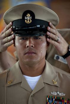 Chief Information Systems Technician Joseph Valencia, assigned to Navy Marine Corps Intranet Detachment San Diego, sheds tears as his mentor places the cover of a chief petty officer on his head for the first time.