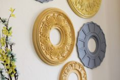 Ceiling medallions make inexpensive and lovely wall decor when painted. -Or left white if your walls are colored. You could even put mirrored glass behind the center holes.