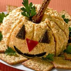 Jack o Lantern Cheeseball (2 cp Shredded Taco Cheese    1/2 pkg Cream Cheese    1/4 cp Solid Pack Pumpkin    1/4 cp Apricot Preserves    1/4 tsp Ground Allspice    1/4 tsp Ground Nutmeg    1 Price Pretzel Rod broken in half    Canned and Pitted Black Olives    Pumpernickel Bread    Red Bell Pepper    sprig Fresh Parsley)