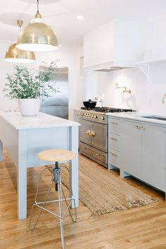 Modern gold lighting and an airy white kitchen: http://www.stylemepretty.com/living/2016/07/25/30-dream-kitchen-moments-thatll-make-you-want-to-renovate/