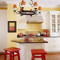 Kitchen Re-do with Quick, Budget-Friendly Changes: A basic, timeless color scheme, such as yellow walls and white cabinetry, lends itself to easy, low-cost changes with accessories. Bar stools painted glossy tomato red, chandelier shades stamped with a checkerboard pattern of red and yellow, and artwork in a red-and-yellow theme energize this kitchen with a lively, warm mood.