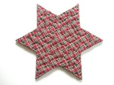 Pretty patchwork for Christmas decor, this rustic quilted table mat trivet measures 11 1/2 inches from point to point and 6 3/4 inches at its lowest width.  It is made up of an assortment of holiday themed calico cotton, homespun and unbleached muslin in a star pattern. The backing is a deep red cotton homespun plaid with green and black.   It has been entirely hand pieced then hand quilted with a primitive utility stitch using heavy green quilting thread.  A layer of thick polyester batting…