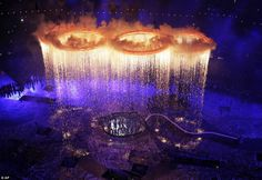 The Olympic rings are illuminated with pyrotechnics as they are raised above the stadium during the Opening Ceremony