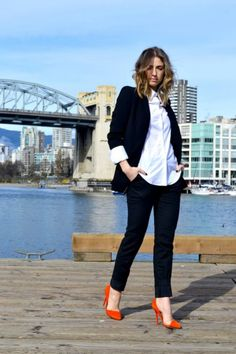 Long menswear black blazer, white cotton blouse with cuffs folded over the blazer, straight-leg black/dark navy trousers, and bright orange d'orsay pumps.