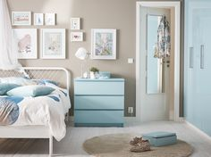 A small bedroom furnished with a bed for two in white metal with square patterned metal bars in the headboard. Shown together with a light turquoise chest of drawers and bedlinen in white and turquoise.