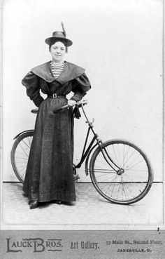 """""""Cabinet card portrait of a young woman posed with a bicycle, Zanesville, Ohio, ca. 1896-1897. The card advertises the Lauck Brothers Art Gallery at 77 Main St., Second Floor, Zanesville, Ohio.""""    (Ohio Historical Society, Norris Schneider Collection, OHS: AL02731.tif.)"""