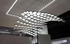 Manta Rhei, ART+COM :: The luminaire consists of 14 1.2-meter long, flexible metal lamellas each of which carries ten paper thin OLED-modules. Thin steel wires attach the blades to small motors hidden in the ceiling.