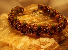 """OXO Real Jasper and Hematite Beads Woven with the hugs & Kisses pattern, other beads are green, amber, and metallic brass seed beads. Chunky style bracelet. 8"""" with antiqued brass clasp. The Jasper beads are so colorful! The pictures really don't do it justice!!!"""
