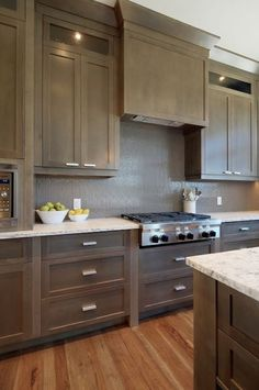 Veranda Interiors: Contemporary gray kitchen design with gray kitchen cabinets & kitchen island, Bianco ...