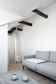 white walls, pale floors, dark beams & grey sofas. Need to switch our covers to grey asap!