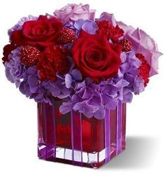 Teleflora's original gift arrangement in a red glass square vase of purple hydrangea, red and lavender roses, and burgundy scabiosa
