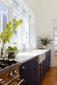 Love this deep, white kitchen sink + dark wood cabinets.