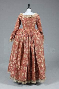 Back view open robe and petticioat, 1760s. Dark cinnamon silk brocaded with trails of ivory blooms, with original braid trimmed engageants, 1880s added gold satin trimming; with a quilted pale blue silk petticoat