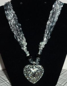 Silver metal Puff Heart pendant with 'jewels', accented with black faceted glass accent beads.  This is a 'slider' necklace. It has a bead at the joining which can be slid up or down to allow you to wear the necklace long or short! Made with trellis, silk and metallic yarns.