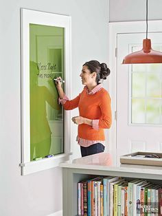 Paint the backside of a piece of glass, frame it, and you have a new take on a message board. And the funner the color, the better. We painted our glass in a peppy green, which pops in a gray and white kitchen. A frame around our glass gives the simple piece a custom feel, plus a ledge for housing markers.Messages written in dry-erase markers wipe away easily