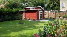 Pultdach Gartenhaus in Schwedenrot in einem einladenden Garten.