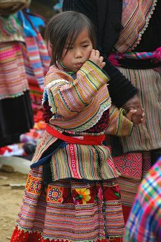 Young Indigenous Girl - Bac Ha, Vietnam  A young girl, wrapped from head to toe in embroidery, walks with her mother through the Bac Ha Mark...