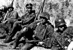 Waffen SS troops take a breather during fighting around Sevastopol in the Crimea in 1942. The officer (3rd from left) is war correspondent Friedrich Zechackel (?). The Russians resisted fiercely but the city fell in early July 1942, after nearly six months of bitter struggle.