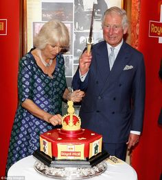 The royal beamed as he wielded an impressive cake knife intended to cut a red and gold gateau made in tribute of the postal service celebrations