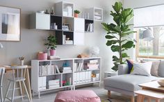 A bright living room with white open shelf unit combined with wall cabinets in white and grey, some with doors and some open.