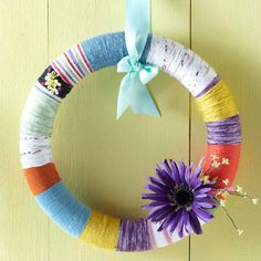 Yarn-Wrapped Spring Color Wreath - Accent a spring door with this easy-to-make wreath made from various colors of yarn. Take a foam wreath form and mark on the front where you want to change up colors. Then take multiple colors of worsted-weight yarn and start wrapping -- that's all there is to it!
