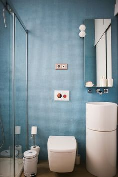 House Tour: A Modern Spanish Home With Floral Motifs | Apartment Therapy - This ultimate minimal and simple bathroom leaves no room for clutter. Floor to ceiling pale blue mosaic tiles surround you with an accessible and open shower while simple and modern white fixtures fill the space.