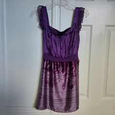 """JUST REDUCED! Purple print top Purple wide strap top has sheer ruffles on straps. Top part has soft pleats in front and elastic in back then falls from waist to flowy bottom with screen print in shadesof purple. Belt attaches in front and ties in back. Small pull/run across front.  Measures 17"""" flat from armpit to armpit, stretches to max. appx 20"""", same with Empire waist band Length of strap on front from top of shoulder to top of part that goes across chest is 6"""". Length from empire waist…"""