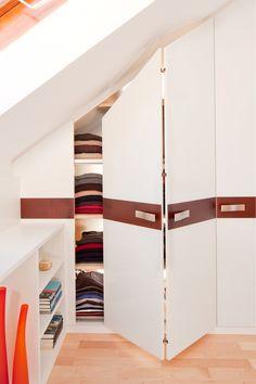 Faltschiebetüren in der Dachschräge sorgen für optimale Übersichtlichkeit und Erreichbarkeit der Kleidung.